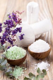 Meersalz in der schüssel, aromaöl in flaschen, wellness und blumen auf grauem strukturiertem hintergrund und blumen auf weinlesehintergrund. selektiver fokus.