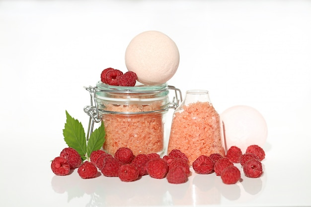 Meersalz mit himbeerextrakt. berry kosmetik. rosa badesalz in gläsern und himbeeren.