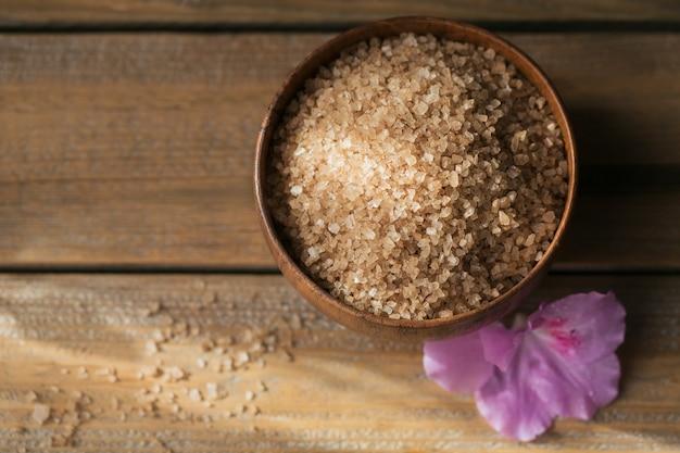 Meersalz, natürliche handgemachte seife, natürliches kosmetiköl und bunte handtücher mit azaleenblüten auf rustikaler holzoberfläche. gesunde haut-, gesichts- und körperpflege. spa- und saunakonzept