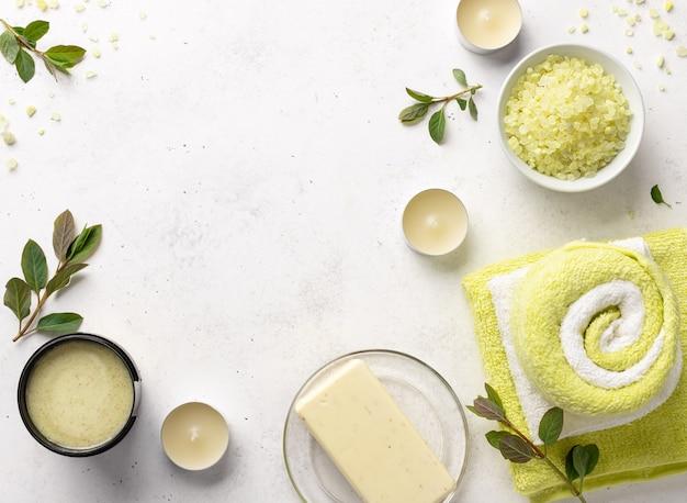 Meersalz, peeling, feste seife und badetücher auf weißem steinhintergrund mit kerzen und grünen blättern. schönheits- und modekonzept mit spa-set.