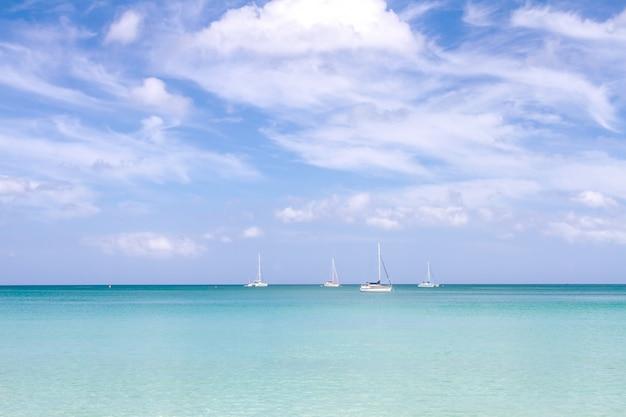 Meersandhimmel und weiche welle von blauem ozean am sommertag des sandigen strandes