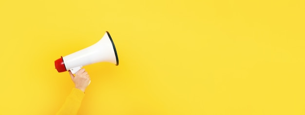 Megaphon in der hand auf gelbem grund, aufmerksamkeitskonzept