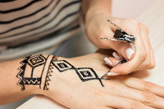 Mehendi-künstler der jungen frau, der henna auf der hand malt