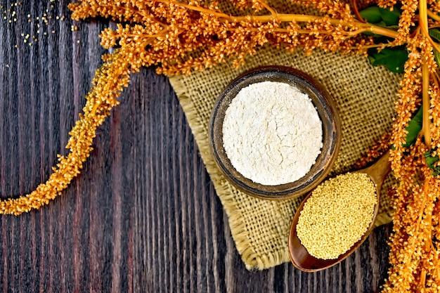 Mehl amaranth in einer tonschüssel, ein löffel mit korn, braune blume mit blättern auf einer serviette aus einem sack auf einem hintergrund von holzbrettern oben