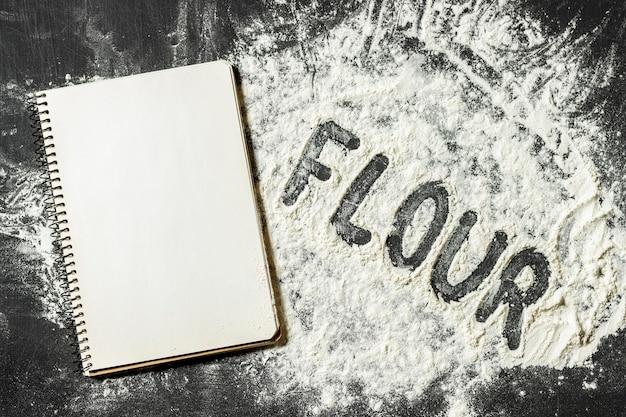Mehl auf dem schwarzen hintergrund mit leerem leerem notizblock