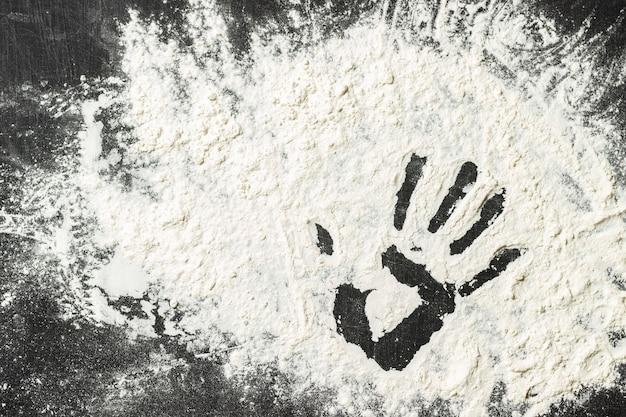 Mehl auf der schwarzen oberfläche mit handzeichen