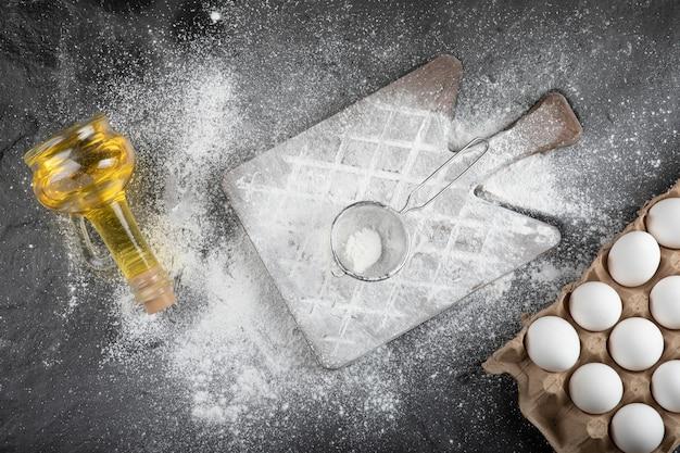 Mehl auf holzbrett verschüttet, rohe eier und öl auf schwarzer oberfläche