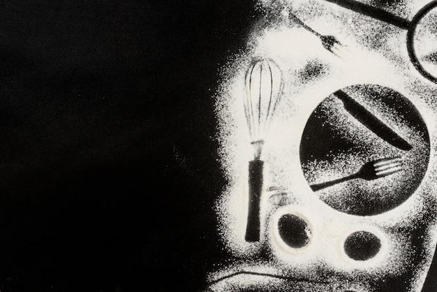 Mehl auf schwarzem hintergrund mit formen von küchenelementen