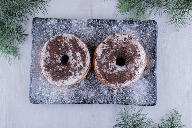 Mehl bedeckte platte mit zwei donuts oben auf weißem hintergrund.