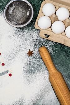 Mehl, beeren und anissterngewürze als dekoration und nudelholz, eier, sieb