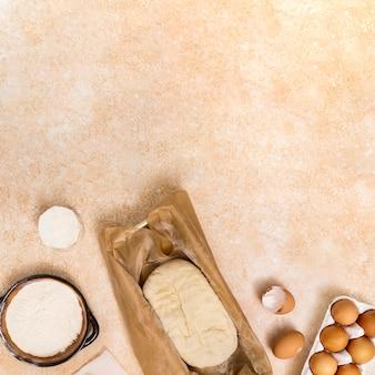 Mehl; ei; gekneteter teig auf beige strukturiertem hintergrund