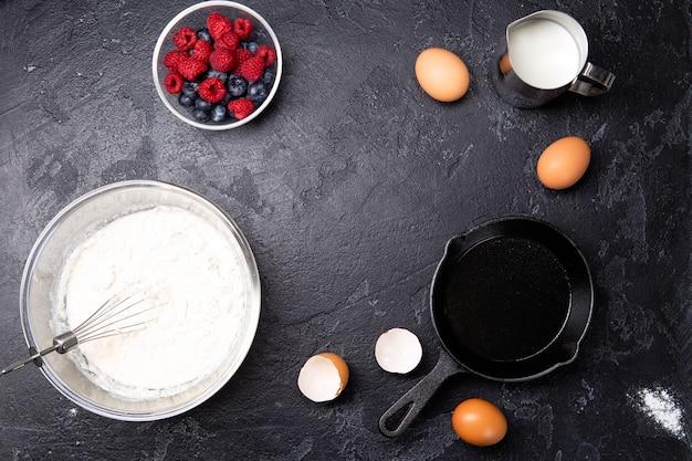 Mehl, eier, beeren, johannisbeeren auf leerem schwarzem tisch in der küche