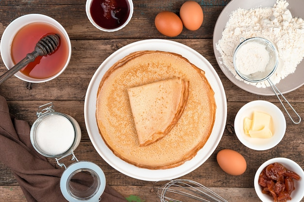 Mehl, eier, honig, zucker und ein stapel gebratener pfannkuchen auf einem braunen hintergrund.