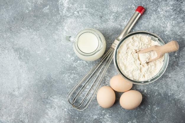 Mehl, eier, milch und whisker auf marmor.