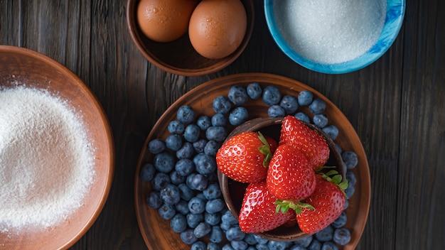 Mehl, eier, zucker, eier und frische beeren sind die zutaten für einen köstlichen kuchen. heidelbeerkuchen