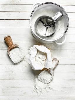 Mehl im beutel mit einer schaufel auf einem weißen holztisch
