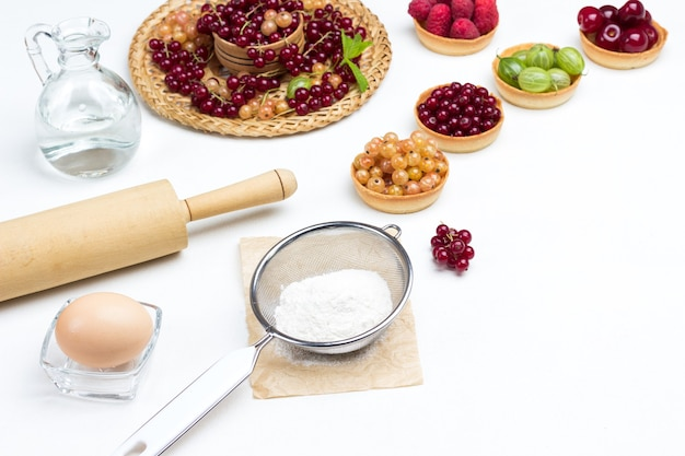 Mehl im sieb, nudelholz und ei in einer kleinen glasschüssel mehlieren. mit wasser dekantieren. törtchen mit beeren. weißer hintergrund. ansicht von oben