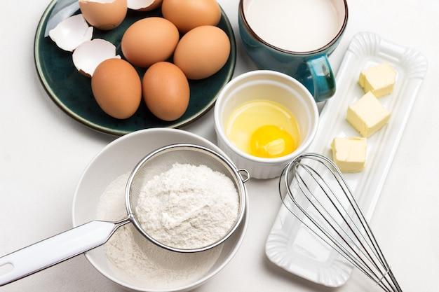Mehl im sieb und in der schüssel. butter und schneebesen auf teller. eigelb in schüssel. milch im blauen becher. braune eier auf blauem teller. weißer hintergrund. draufsicht