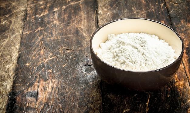 Mehl in eine schüssel geben. auf einem hölzernen hintergrund.