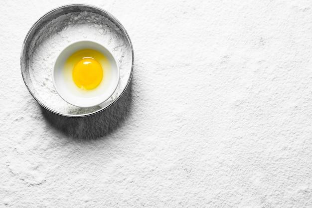 Mehl in einem sieb mit ei in einer schüssel.