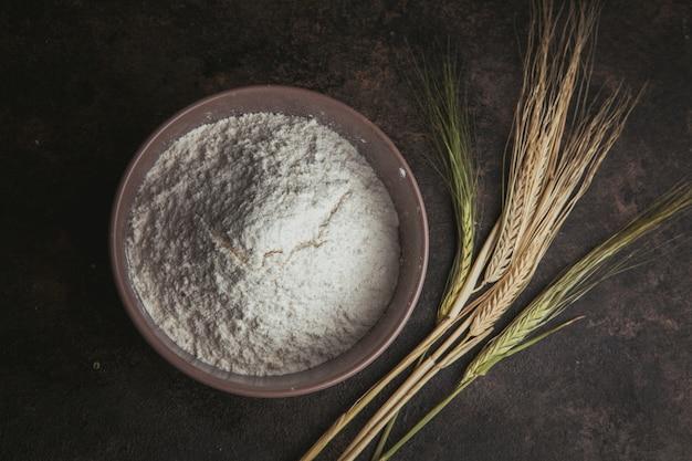 Mehl in einer schüssel mit weizen flach lag auf einem dunkelbraunen