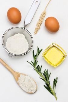 Mehl in holzlöffel olivenöl und quelle von rosmarinsieb und glas ei und ährchen von weizen weiße oberfläche draufsicht
