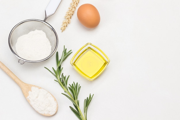 Mehl in holzlöffel, sieb und glas, olivenöl und rosmarinzweig, ei und ährchen weizen