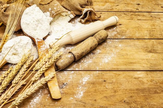 Mehl in säcken, ähren, löffeln und hölzernen nudelhölzern. backkonzept, holztisch, kopierraum