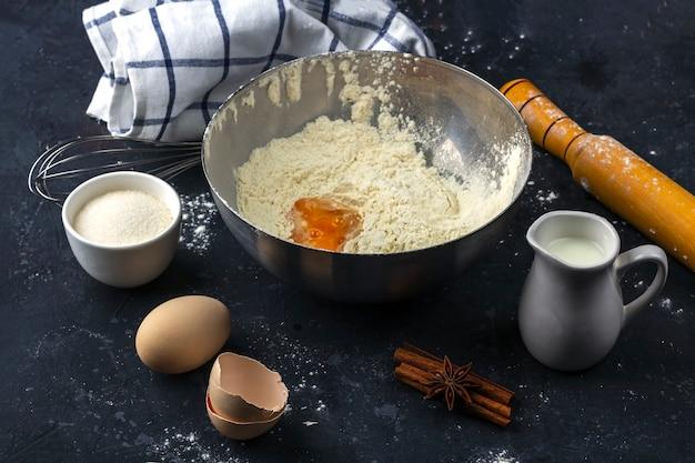 Mehl mit ei in einer metallschüssel zwischen zutaten und utensilien zum kochen von kuchen auf einem dunklen tisch. konzept der herstellung von teig zum backen. nahansicht