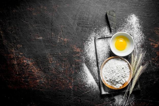 Mehl mit ei und ährchen auf schneidebrett auf dunklem rustikalem tisch