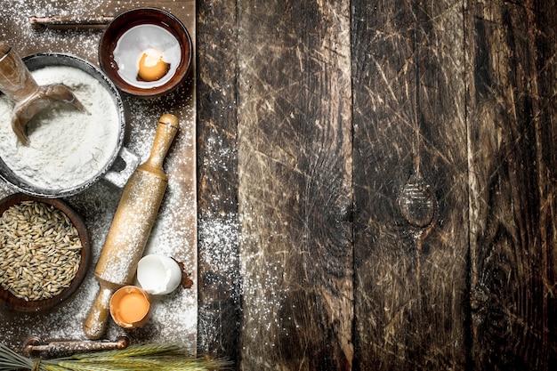 Mehl mit frischen eiern. auf einem hölzernen hintergrund.