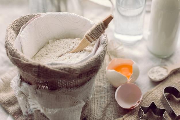 Mehl mit löffel in einem sack und zerbrochenem ei