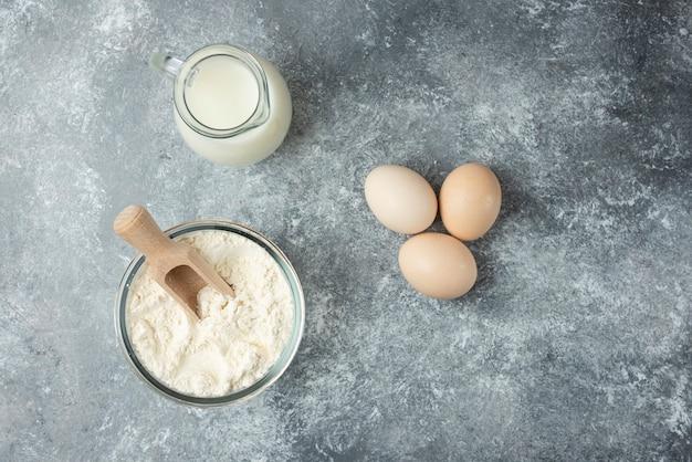 Mehl, rohe eier und milch auf marmor.