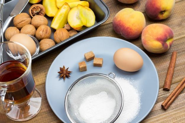 Mehl, sieb und ei auf teller. pfirsiche und walnüsse im backblech. geschnittene pfirsiche in einer schüssel. glas tee und zimtstangen auf dem tisch.