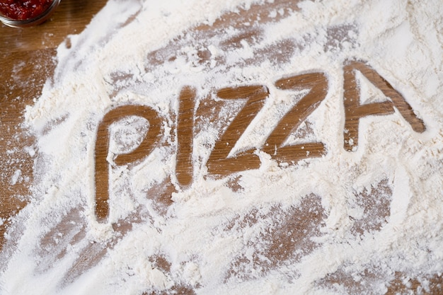 Mehl und die worte pizza sind auf dem tisch verteilt. zutat für die herstellung von italienischem gebäck. konzept für die zubereitung von speisen.
