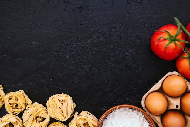 Mehl und eier in der nähe von pasta und tomaten