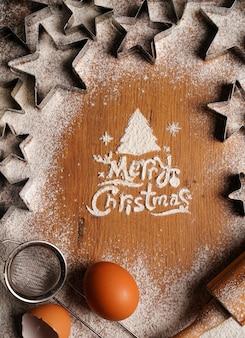Mehl- und keksformen auf einem holztisch und die aufschrift frohe weihnachten. foto in hoher qualität