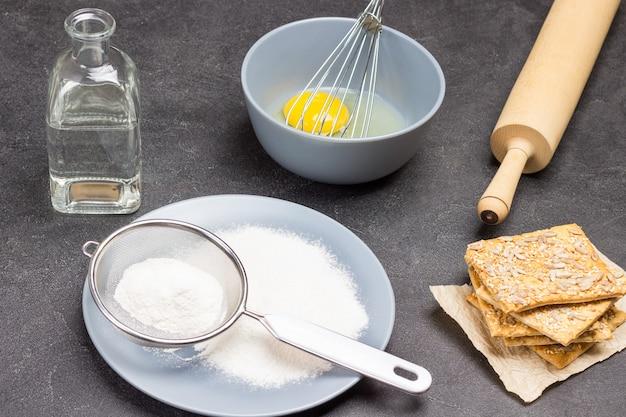 Mehl und sieb auf grauem teller. kekse und nudelholz auf dem tisch. wasserflasche. zerbrochenes ei und in einer schüssel verquirlen. schwarzer hintergrund. ansicht von oben
