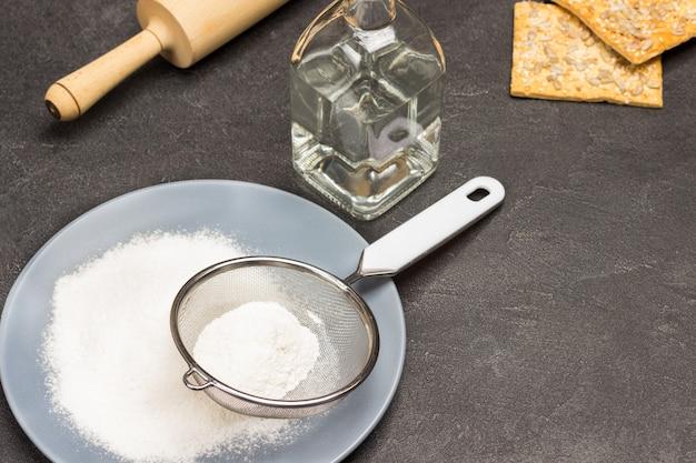 Mehl und sieb auf grauem teller. wasserflasche, kekse und nudelholz auf dem tisch. schwarzer hintergrund. ansicht von oben