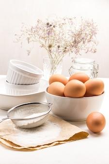Mehl und sieb auf papier. das ei liegt auf dem tisch. braune hühnereier in der schüssel. weiße keramikschalen. weißer hintergrund.