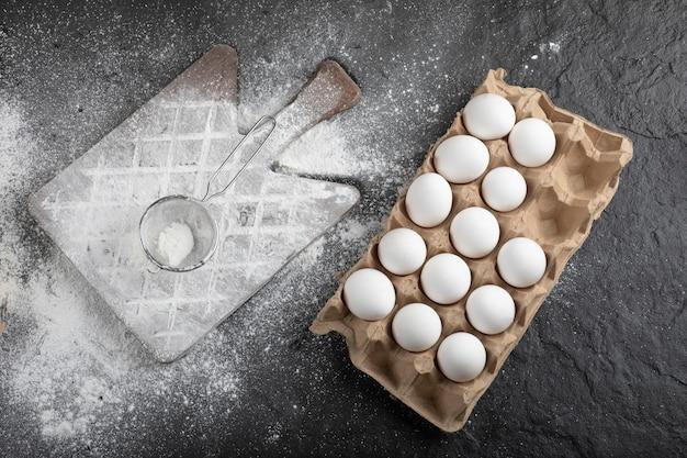 Mehl verschüttet auf holzbrett und rohe eier auf schwarzer oberfläche