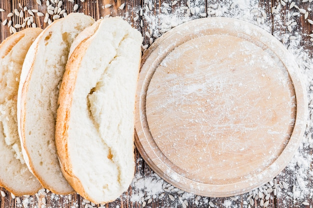 Mehl verteilt sich über das runde schneidebrett über den tisch