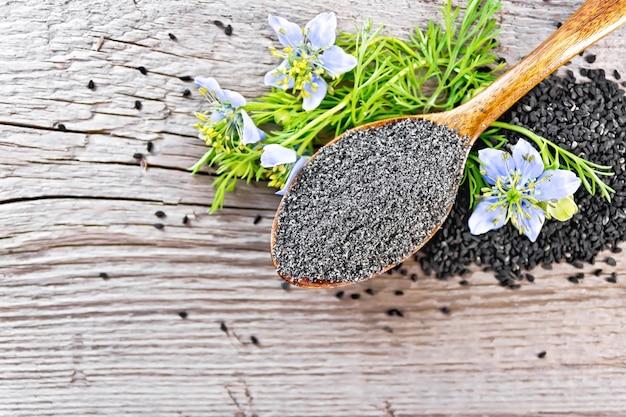 Mehl von nigella sativa im löffel mit einer blume und blättern von kalingini auf einem alten holzbrett von oben