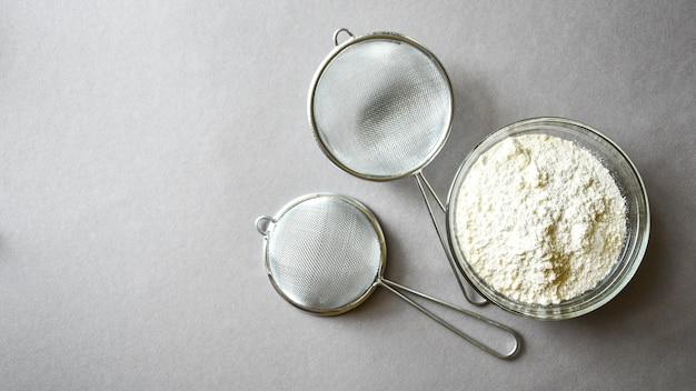 Mehl zum backen auf grauem hintergrund vorbereitet. kopieren sie platz für text. rezept zutat