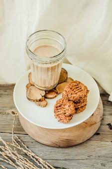 Mehlfreie glutenfreie erdnussbutter, haferflocken und dattel mit einem glas milch auf holz