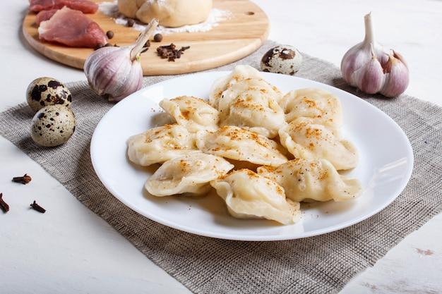 Mehlklöße mit bestandteilen (fleisch, teig, gewürze) auf einer leinentischdecke auf weiß