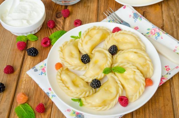 Mehlklöße mit hüttenkäse, frischen beeren und sauerrahm auf einer weißen platte. traditionelles ukrainisches und russisches gericht.
