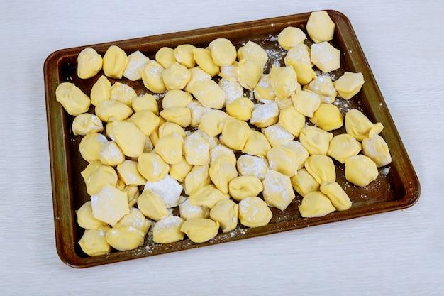 Mehlklöße roh auf einem hölzernen brett. traditionelles hausgemachtes essen. der prozess des kochens von mehlklößen.