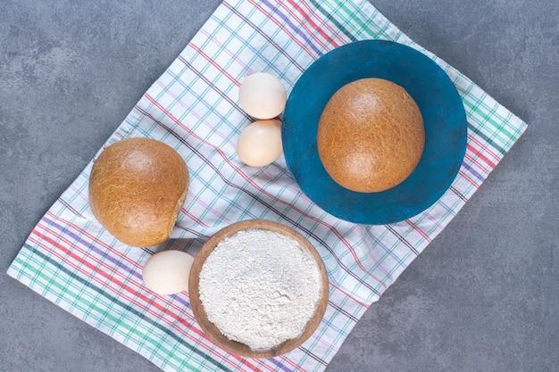 Mehlschüssel, eier und brötchen auf einem handtuch auf marmorhintergrund. foto in hoher qualität
