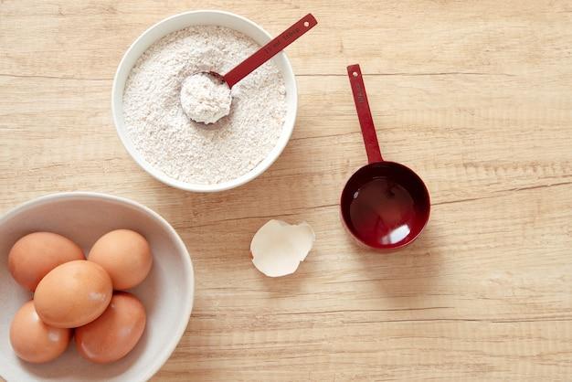 Mehlschüssel mit rotem messlöffel und schüssel mit eiern
